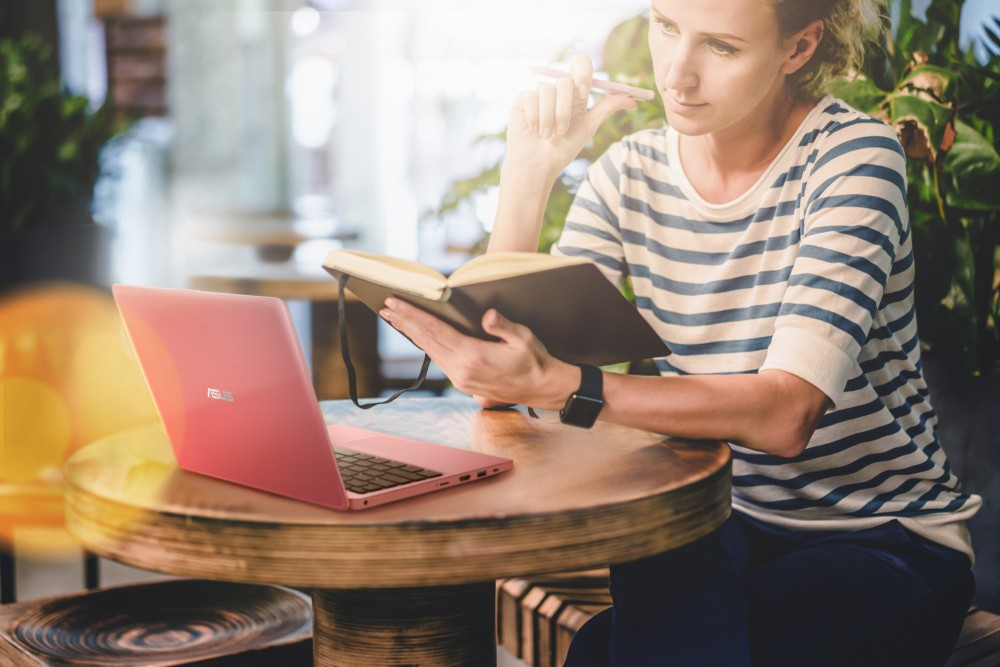 Young woman in striped t-shirt sitting at round wooden table in cafe and holding notebook and pen. In front of her is laptop, smartphone. Freelancer working outside home. Student learning online; Shutterstock ID 533639215; PO: 439437361